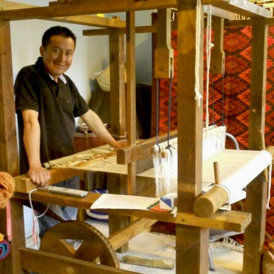 Weaver Francisco Bautistia is standing by his traditional Oaxacan loom in front of a large red tapistry with diamond geometric designs