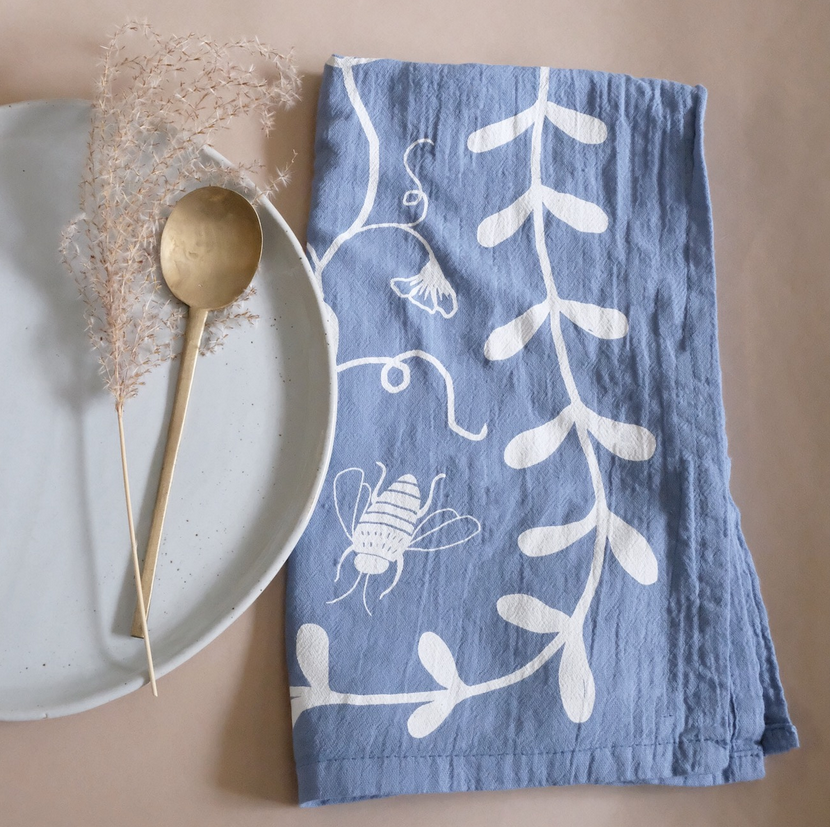 A printed tea towel with a nausturtium design by Elana Gabrielle is set next to a plate and spoon