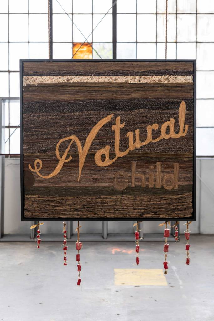A textile artwork installed in a gallery the artwork says the phrase Natural Child and is made from various textures and natural materials in shade of brown by artist Krista Anara Cibis.